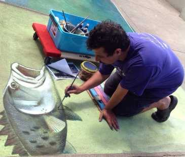 Man painting a picture of a fish on the ground