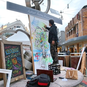 Man doing a live painting in the streets.